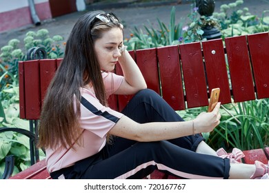 Happy hipster young woman using smartphone in the park