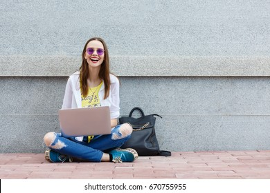 Happy hipster young woman working on laptop on the grey wall background