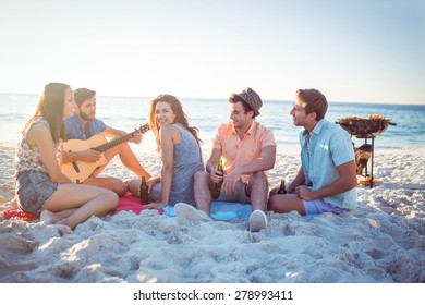 Happy hipsters relaxing and playing guitar at the beach