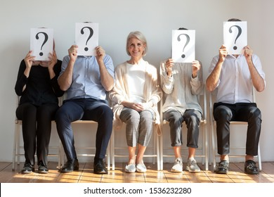 Happy hired employed mature old businesswoman professional chosen candidate sitting among people hiding faces behind questions marks waiting for job interview, human resource, recruit choice concept