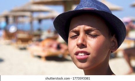 Happy hispanic boy with hat smiling on beach and give a kiss to camera