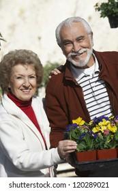 Happy Hispanic couple with flower pots at botanical gardens