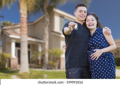 Happy Hispanic Couple In Front of New Home Showing Off Their House Keys.