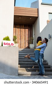 Happy Hispanic couple hugging in front of new house
