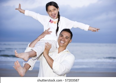 Happy Hispanic dad and 9 year old daughter having fun on beach
