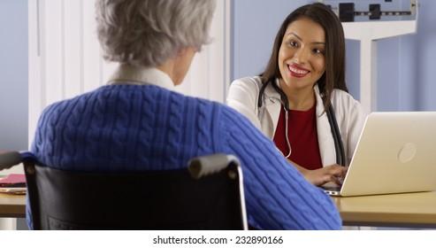 Happy Hispanic doctor talking with senior patient