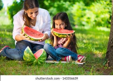 Happy hispanic family eating watermelon at park