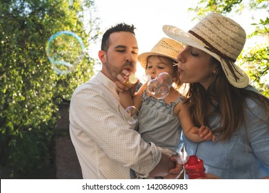 Happy Hispanic Family Having Fun Together Outdoors. Lovely Family Spending Time Together in the Park. Cute Spanish Couple Playing with Bubbles . Family Concept.