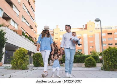 Happy Hispanic Family Lifting Their Daughter Outdoors. Lovely Family Spending Time Together in the Park. Cute Spanish Couple Playing with their Kids Outdoors. Family Concept.