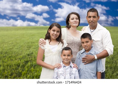 Happy Hispanic Family Portrait Standing in Grass Field.