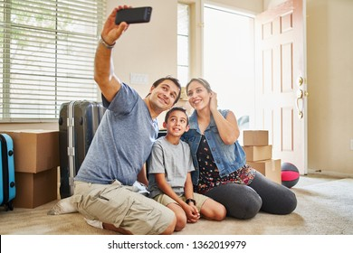 happy hispanic family taking selfie after moving into new house