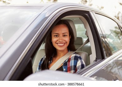 Happy Hispanic female driver in a car