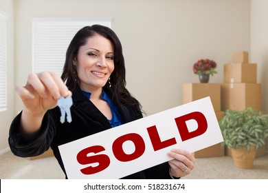 Happy Hispanic Female Real Estate Agent with Sold Sign and Keys in Room with Moving Boxes.