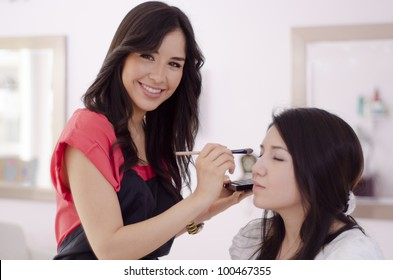 Happy hispanic makeup artist applying makeup on a client