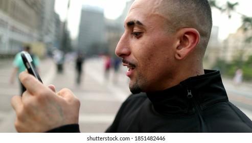 Happy hispanic man receiving good news on smartphone celebrating