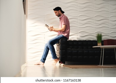 Happy hispanic man sitting on sofa at home with digital tablet. Latino guy watching movie on computer and laughing.