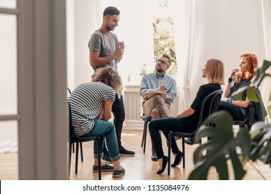 Happy hispanic man talking to his support group about his successful fight with drug addiction