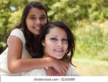 Happy Hispanic Mother and Daughter in the Park.
