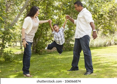 Happy Hispanic Mother and Father Swinging Son in the Park.