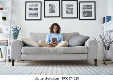 Happy hispanic teen girl holding pad computer gadget using digital tablet technology sitting on couch at home. Smiling young woman using apps, shopping online, reading news, browsing internet on sofa.