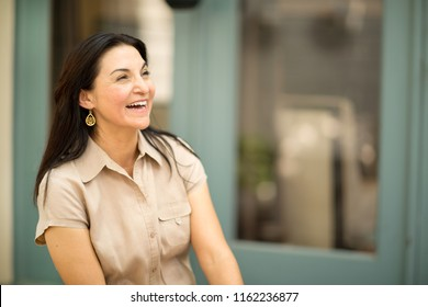 Happy Hispanic woman laughing.