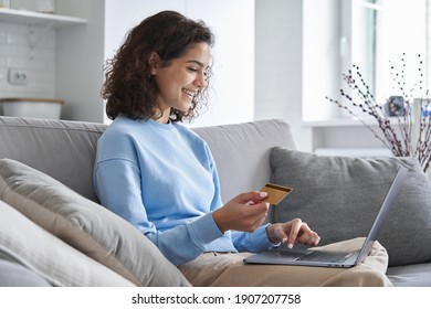 Happy hispanic young woman consumer holding credit card and laptop buying online at home. Female shopper customer shopping on ecommerce website market place making digital payment using bonus money.