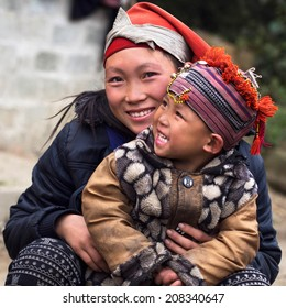 Happy Hmong woman and child smiling, sitting outside at Giang Ta Chai village near the hill town of Sapa, Lao Cai Province, North Vietnam.