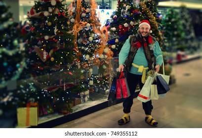 Happy hobo in santa hat holds shopping bags standing on Christmas trees background