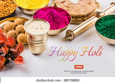 Happy Holi greeting card designed showing Indian traditional sweet and salty food, flowers and powder colours arranged over white background or clay. Selective focus