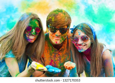 Happy holi party: sunny beautiful woman female teenager and two males men in sunglasses celebrating happy holi festival in spring, summer day outdoor in green park with light leaks and colorful powder