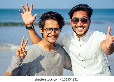 Happy holi two indian stylish mans young friends hugging on the beach by the sea.long-awaited meeting diwali of the brothers in India Goa tropical paradise summer vacation blue sky and ocean