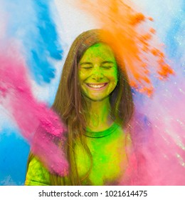Happy holi. Young cheerful girl under explosion of colored powder at Holi colors (paints) party. Freeze motion (stop motion) of color powder exploding or throwing colour powder. Glitter explosion.