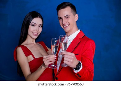 Happy holiday. Beautiful young loving couple in red smiling holding glasses with champagne on blue background.