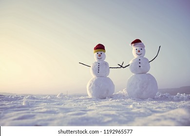 Happy holiday and celebration. Santa claus hat in winter. New year snowmen from snow in santa hat. Snowman couple outdoor. Christmas or xmas decoration., copy space