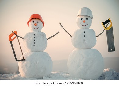 Happy holiday and celebration. Snowman builder in winter in helmet. New year snowman from snow with saw. Christmas or xmas decoration. Building and repair work.