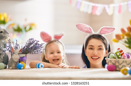 Happy holiday! A mother and her daughter are painting eggs. Family preparing for Easter. Cute little child girl is wearing bunny ears.