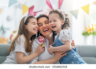 Happy holiday! Mother and her daughters with painting eggs. Family celebrating Easter. Cute little children girls are wearing bunny ears.  - Shutterstock ID 1926842318