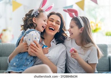 Fröhlicher Urlaub! Mutter und ihre Töchter mit Eiermalerei. Familie feiert Ostern. Kleine süße Mädchen tragen sonnige Ohren.
