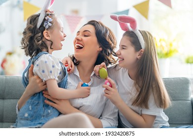 Happy holiday! Mother and her daughters with painting eggs. Family celebrating Easter. Cute little children girls are wearing bunny ears.  - Shutterstock ID 1932420875
