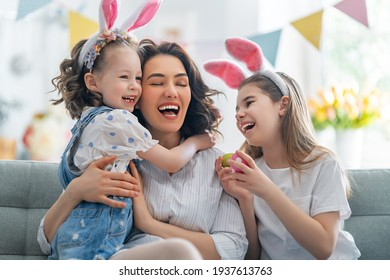 Happy holiday! Mother and her daughters with painting eggs. Family celebrating Easter. Cute little children girls are wearing bunny ears.  - Shutterstock ID 1937613763