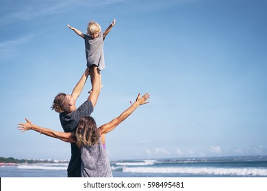 Happy holiday near the sea. Family couple playing with kid on beach.