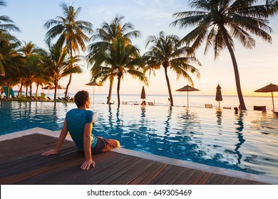 happy holidays in beautiful beach hotel at sunset, man sitting near swimming pool and relaxing
