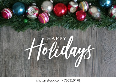 Happy Holidays Calligraphy with Festive Colorful Holiday Christmas Ornament Border Over Garland and Wood Background