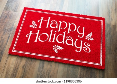 Happy Holidays Christmas Red Welcome Mat On Wood Floor Background.