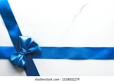 Happy holidays, festive decoration and brand sale promotion concept - Blue silk ribbon and bow on luxury marble background, holiday flatlay backdrop