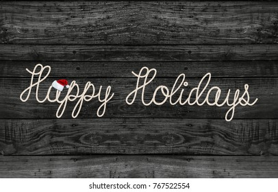 happy holidays greeting rope text on rustic black wood