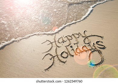 Happy Holidays message handwritten in smooth sand with an oncoming wave in the lens flare of the tropical sun