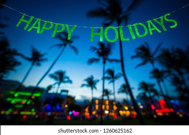 Happy Holidays message hanging in glittery party banner above tropical palm trees of the glowing neon lights of the skyline of Miami Beach, Florida, USA