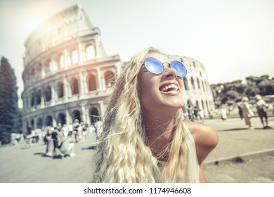 Happy holidays in Rome, smiling young blonde in front of colosseum in Rome in Italy with sunglasses. Intense expression of happiness.