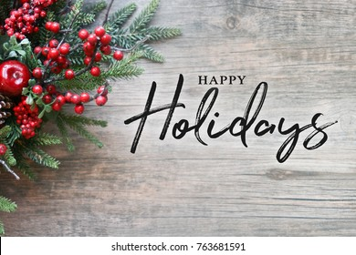 Happy Holidays Text with Christmas Evergreen Branches and Berries in Corner Over Rustic Wooden Background - Shutterstock ID 763681591
